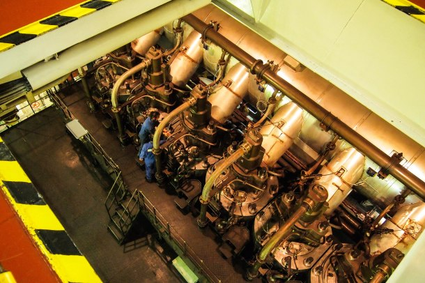 Below deck, two of the engine crew work at cleaning and closing the valves of the main engine's pumps.