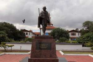 A Gandhi statue ruining what would be a beautiful built landscape in Ghana. A pied crow flies by under a cloudy sky judging those who placed it there. Photo and quotes from http://tinyurl.com/jdv5lt5